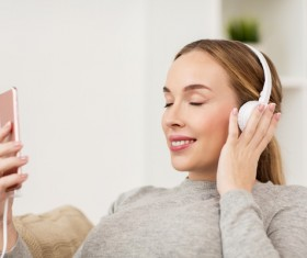 Listening to music with headphones and smartphone Stock Photo