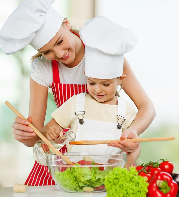 Mom and her daughter mix salad Stock Photo