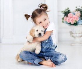 Naughty little girl holding puppy Stock Photo