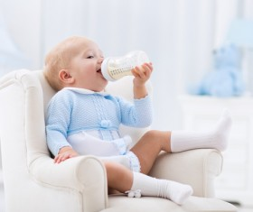 Sitting on a small couch with a baby drinking milk Stock Photo