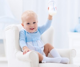 Sitting on a small sofa baby happy holding the bottle Stock Photo