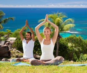 Smiling men and women do yoga together Stock Photo