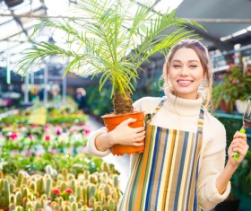 Smiling woman holding potted tropical plants HD picture