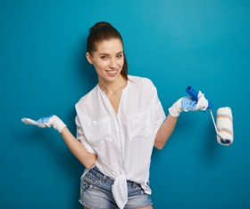 Smiling woman in front of blue wall Stock Photo