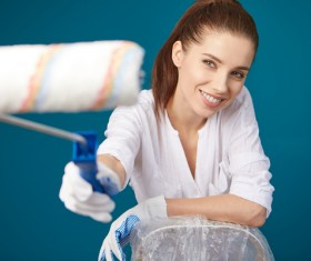 Smiling woman painting the walls of Stock Photo