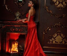 Standing in front of the fireplace red dress woman Stock Photo 01