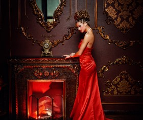 Standing in front of the fireplace red dress woman Stock Photo 02