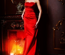 Standing in front of the fireplace red dress woman Stock Photo 04