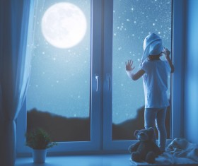 Standing on the windowsill to see the stars of the little girl Stock Photo