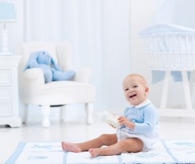 The baby sitting on the carpet is happy to play the bottle Stock Photo