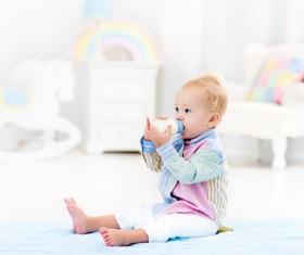 The baby sitting on the floor drinking milk Stock Photo