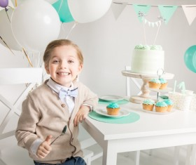 The little boy at the birthday table Stock Photo