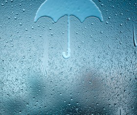 Water droplets and umbrellas on glass windows Stock Photo