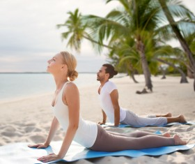 Yoga exercise men and women on the beach Stock Photo