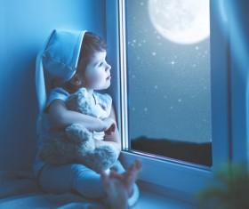 little girl sitting on the windowsill watching the stars Stock Photo