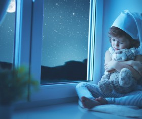 little girl sitting on the windowsill with a teddy bear Stock Photo