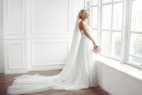 Beautiful bride standing at the window Stock Photo 02