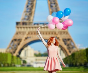 Holding a balloon young girl with the Eiffel Tower background HD picture
