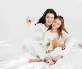 Mother and daughter sitting on the bed HD picture