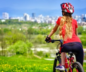 The woman riding a bike looks at the distant city Stock Photo
