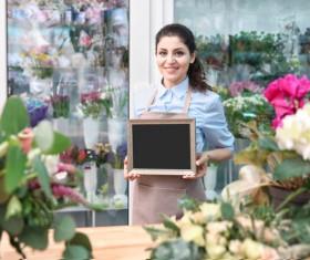 Working in a flower shop Woman hand holding a blackboard Stock Photo