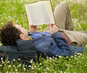 Young man lying on the lawn reading Stock Photo