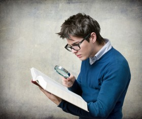 Young man with a magnifying glass to read Stock Photo