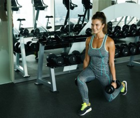 woman holding a dumbbell in the gym Stock Photo 01