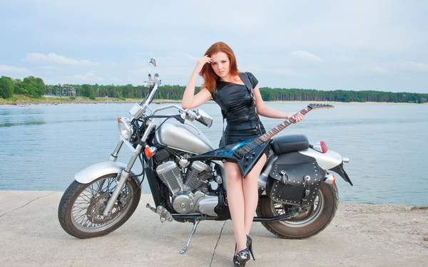Holding an electric guitar leaning against a motorcycle woman Stock Photo