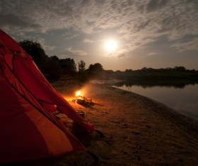 Lakeside camping tents with bonfire Stock Photo
