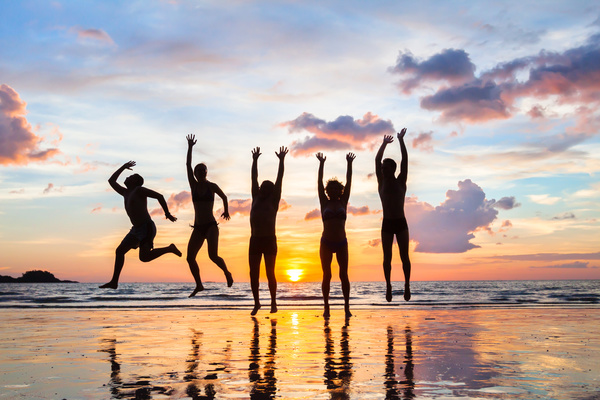 group of people jumping on the beach at sunset ...