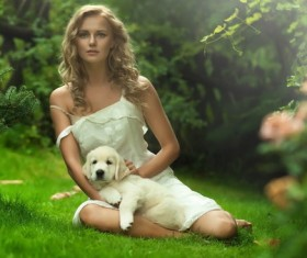 The woman sitting on the grass is holding the dog Stock Photo