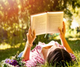 woman lying on the grass reading Stock Photo
