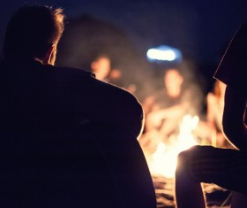young man sitting next to the campfire Stock Photo 01