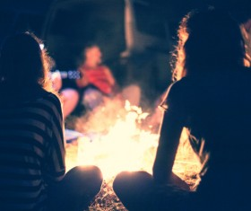 young man sitting next to the campfire Stock Photo 02