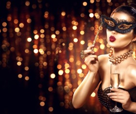 Beautiful woman holding champagne with masks Stock Photo