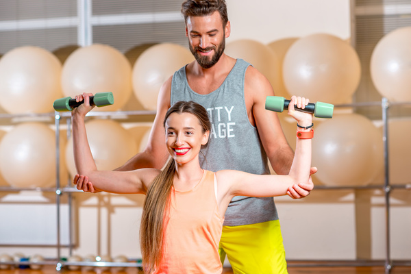 Woman with trainer in the fitness room