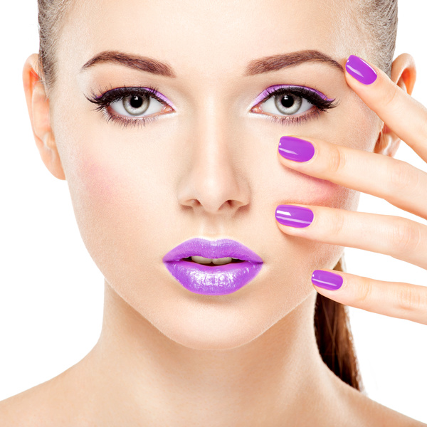 face of a beautiful  girl with violet  lips and bright pink  nails.