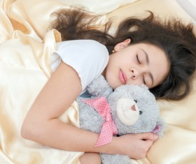 The little girl who sleeps around the teddy bear Stock Photo