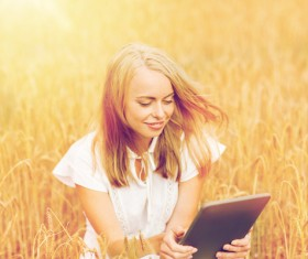 A woman using a tablet in the wheat field Stock Photo