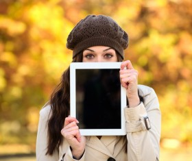 A woman who covers her face with a tablet computer Stock Photo