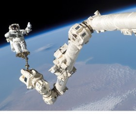 Astronauts on the robotic arm Stock Photo