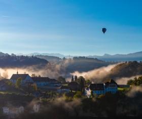 Balloon flying above foggy mountain town Stock Photo