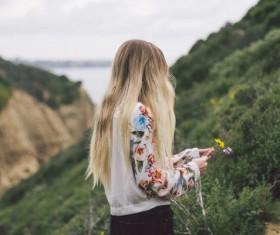 Blonde girl enjoying fresh air on mountain Stock Photo