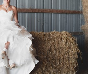 Bride posing with white dress in straw storehouse Stock Photo