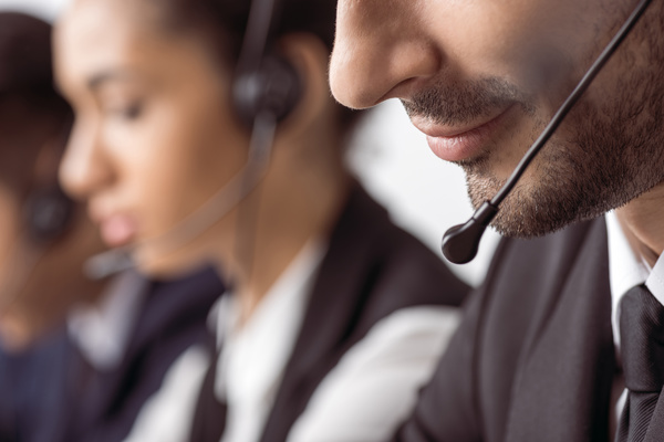 Cropped shot of bearded call center operator in headset working