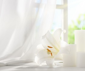 Candles and flowers on the windowsill Stock Photo