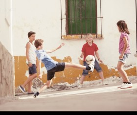 Children playing football in the alley Stock Photo