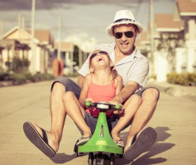 Dad and little girl driving electric toy car Stock Photo