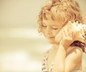 Little girl listening to conch Stock Photo